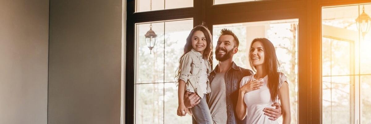 Un couple et sa petite fille dans l'entrée de sa nouvelle maison, un jour heureux et ensoleillé