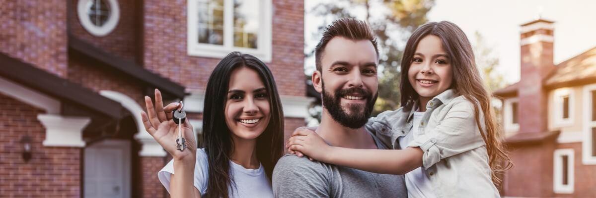 Un couple et sa petite fille devant sa nouvelle maison dont il vient d'obtenir les clés