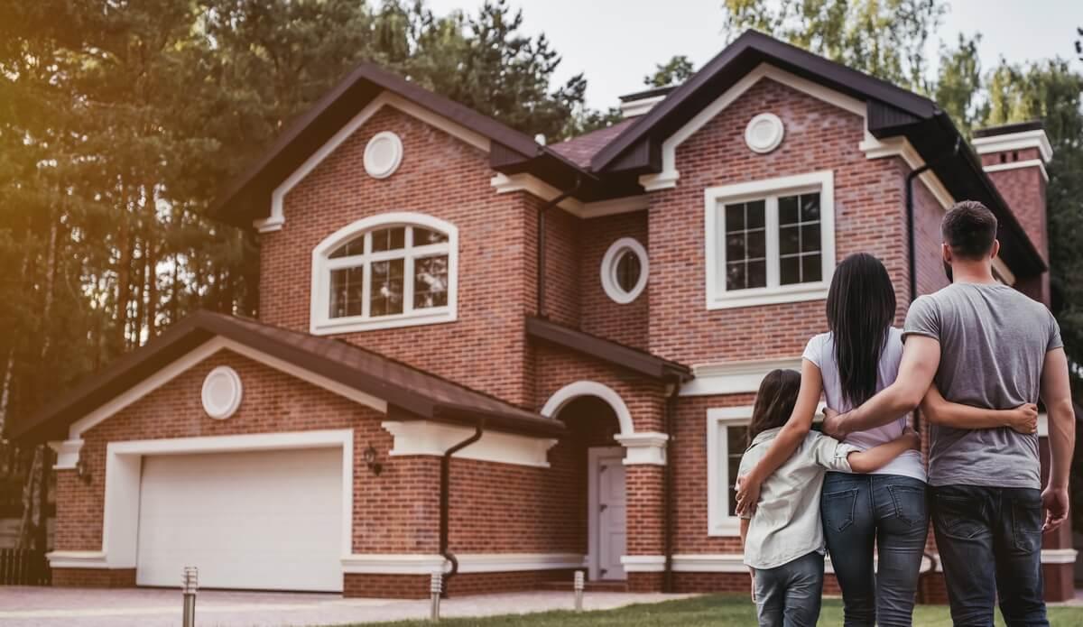 Un couple et sa petite fille de dos, devant sa nouvelle maison dans la campagne toulousaine