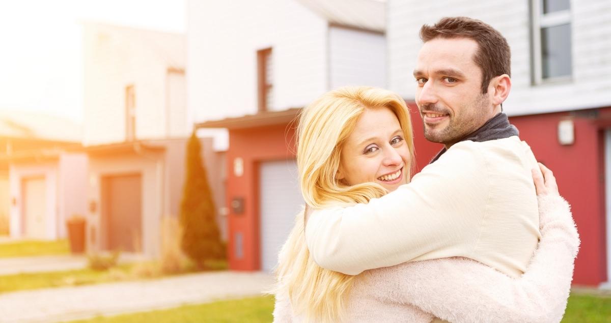 Un jeune couple devant des maisons neuves