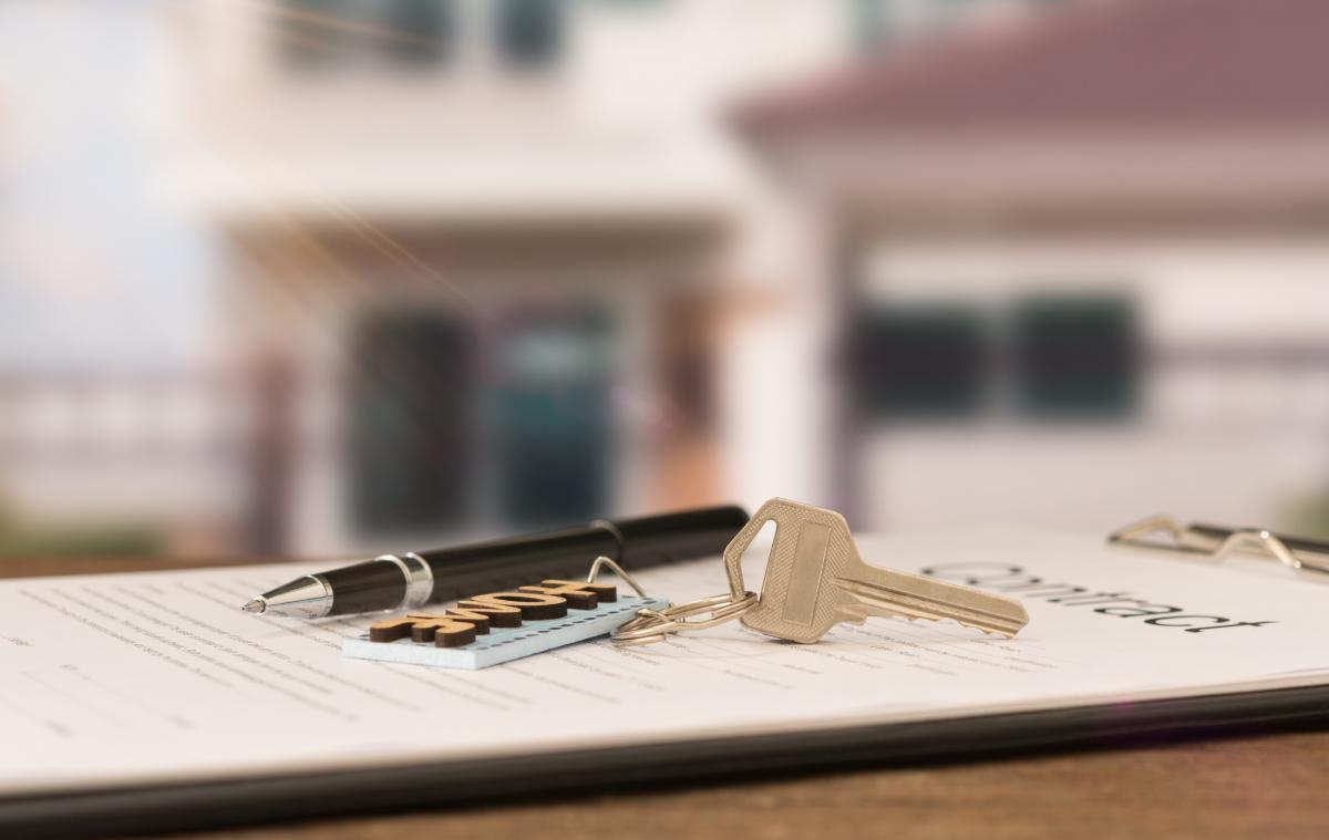 aide achat immobilier neuf - une clé de maison et un stylo sur un acte de vente