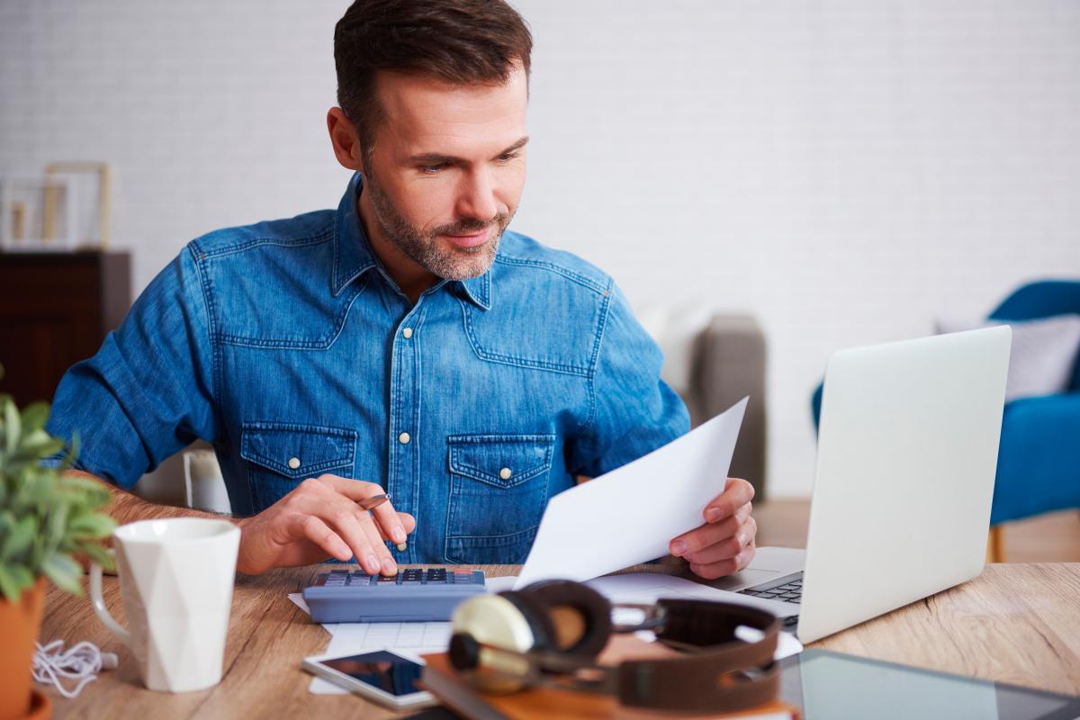 aide achat immobilier neuf - un homme calculant ses mensualités pour son prêt immobilier