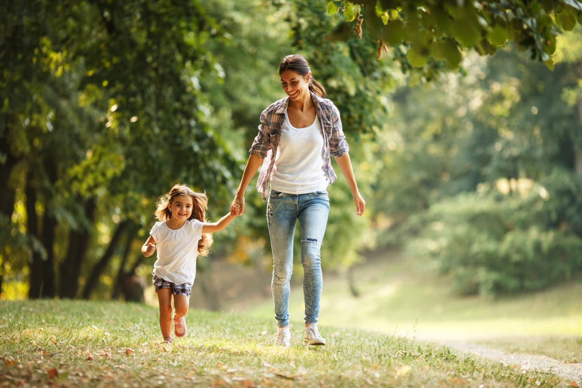 Végétalisation à Toulouse – Une mère et sa fille se promenant dans un parc boisé