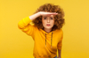 Appartement étudiant à Toulouse – Jeune femme sur fond jaune cherchant quelque chose au loin